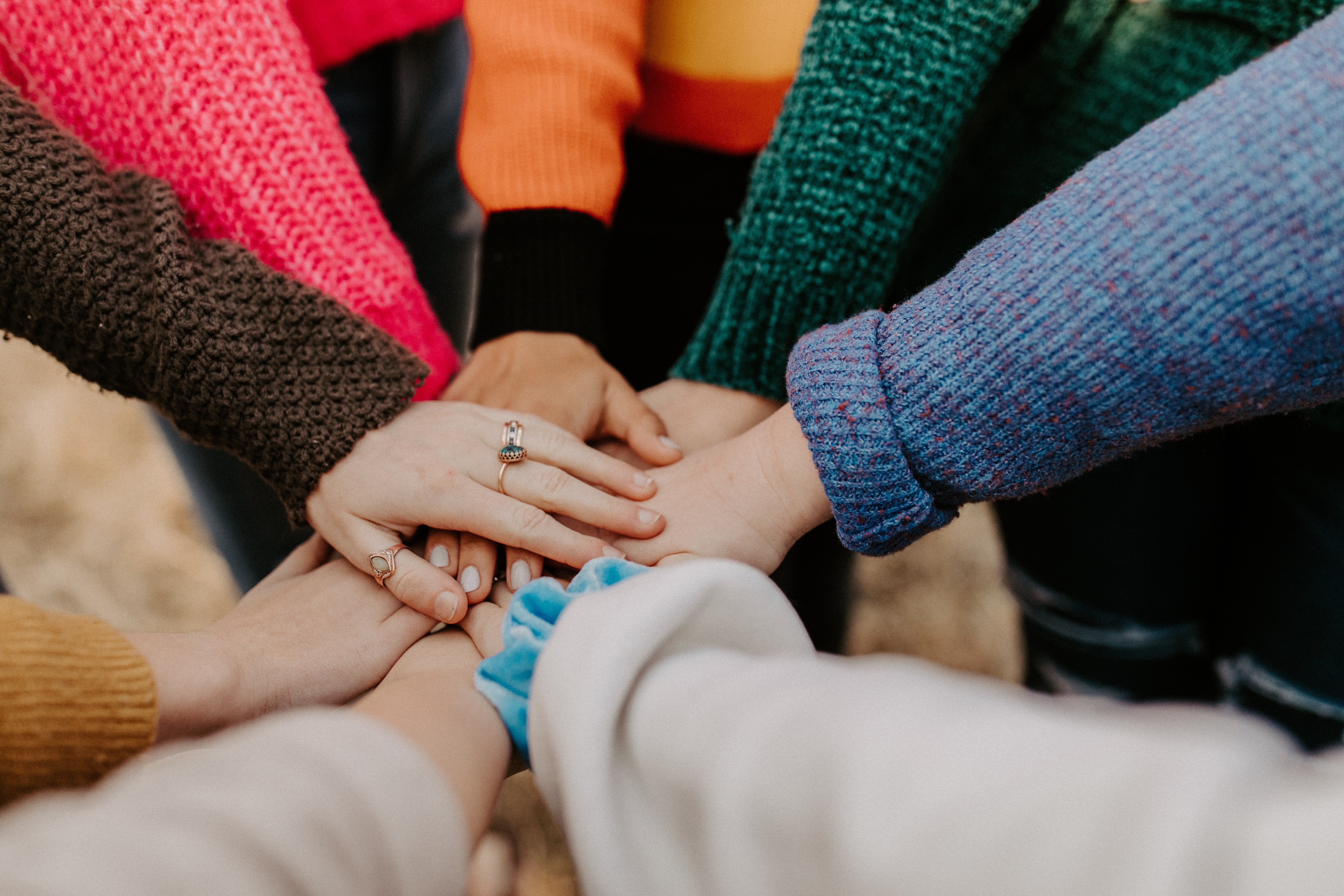 A group of people stacking there hands together as a sign of teamwork.